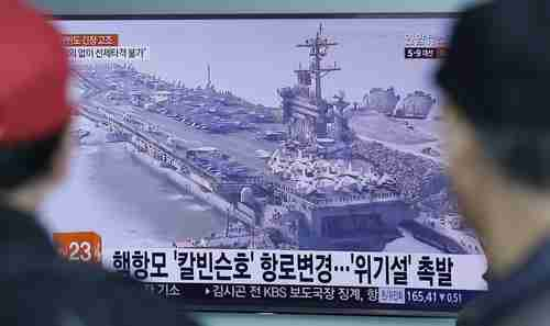 People in Seoul, South Korea, watch a TV news program showing a file image of the USS Carl Vinson aircraft carrier on Wednesday (AP)