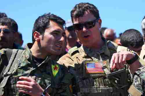 A US officer speaking with a YPG fighter on April 25 (AFP)
