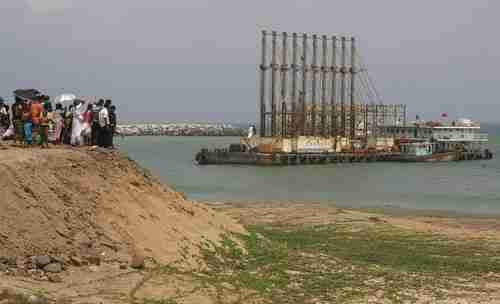 Sri Lankan citizens watch Chinese dredging ships in Hambantota port (Reuters)