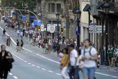 People walk down a main street on Thursday in Barcelona, where a van mounted the sidewalk and ploughed into people. (AP)
