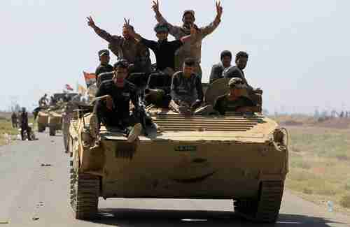 Iraqi forces flash victory sign after defeating ISIS in Hawija (AFP)
