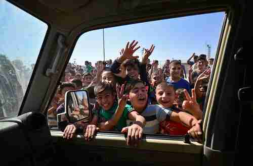 Children greet Iraqi soldiers as they enter the southern outskirts of Kirkuk on Monday (Reuters)