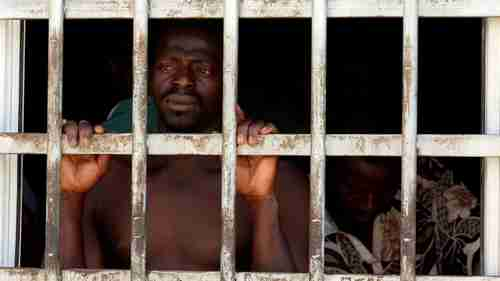 A migrant looks out of a barred door at a detention center in Gharyan, Libya, Oct. 12, 2017. (Reuters)