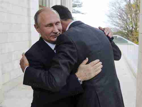 Vladimir Putin and Bashar al-Assad hug and say that the Syria war is at an end (AP)