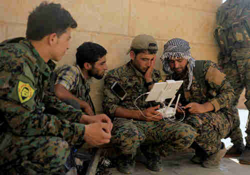 US soldiers train Kurdish SDF forces in how to control a drone (Reuters)
