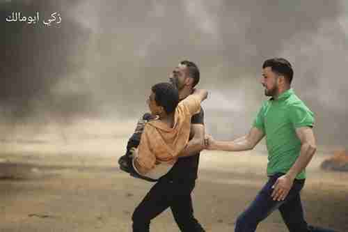 A child is carried by Palestinians away from the front lines after he was shot. The smoke is created by burning tires that the Palestinians use to hide from the Israel troops (Ma'an News)