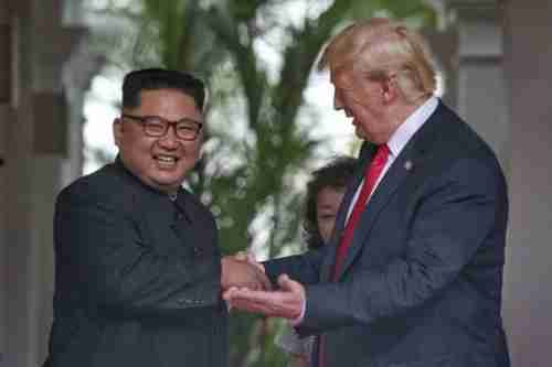 Kim Jong-un and Donald Trump shake hands in Singapore on Tuesday (AP)