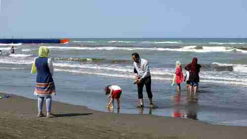 An Iranian family frolicking at the beach in the Caspian Sea port city of Gisum (Getty)