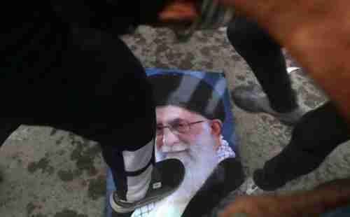 Protesters trample a portrait of Iran's Supreme Leader Ayatollah Ali Khamenei, during the storming and burning of the Iranian consulate in Basra on Friday (AP)