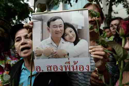 Supporters hold a picture of Thaksin Shinawatra and his sister Yingluck in Bangkok on Aug 5, 2017. (AFP)