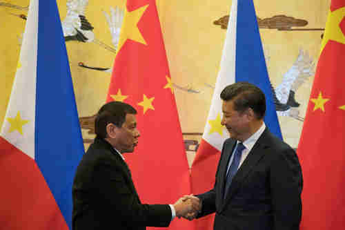 Rodrigo Duterte and Xi Jinping share a warm greeting and handshake (Reuters)