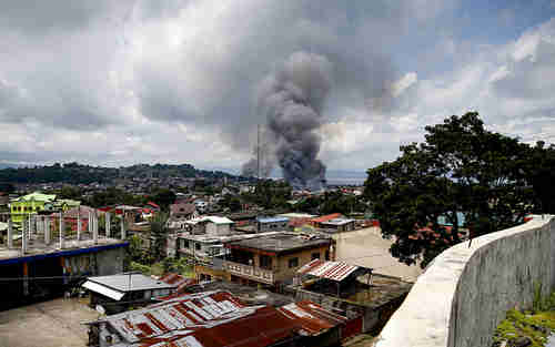 Fire rages at several houses following airstrikes by Philippine Air Force bombers on May 27 (AP)