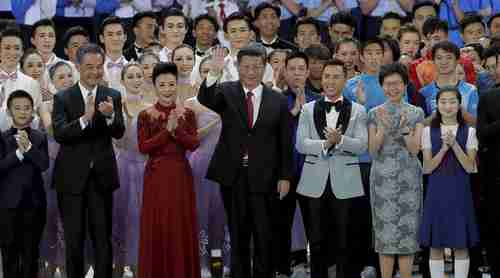 China's president Xi Jinping (center) and his wife in Hong Kong on Friday, surrounded by Hong Kong officials (AP)
