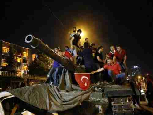 Young men stand on a Turkish army tank in Ankara on July 16, 2016, the day after the attempted coup. (Reuters)