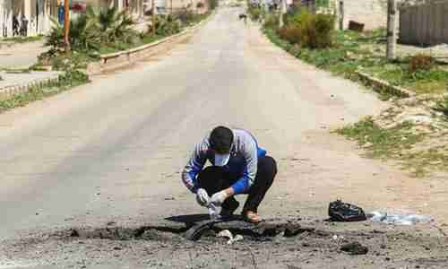 A Syrian man collects samples from the site of the Sarin gas attack in Khan Sheikhoun in April. (AFP)