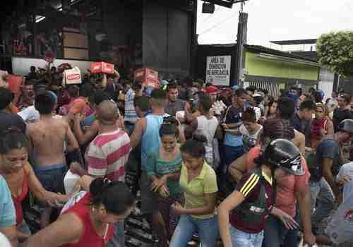 Venezuelans loot a food warehouse in December