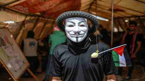 A Gaza protester wears a tire on his head with an onion (to protect himself from tear gas) dangling from it (al-Jazeera)