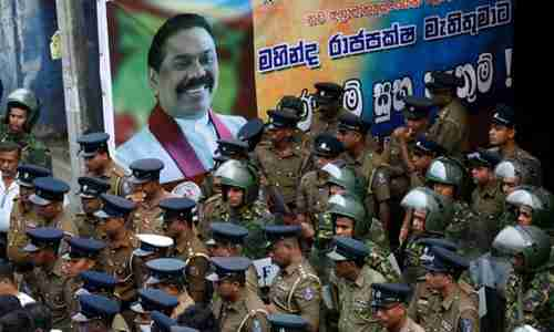 Sri Lankan police and special forces stand guard next to a poster of the newly appointed prime minister, Mahinda Rajapaksa (Reuters)