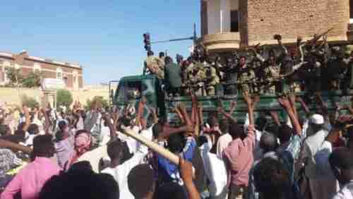 Anti-government protesters in Atbara, Sudan, on 20-Dec wave their hands at security forces (Sudan Tribune)