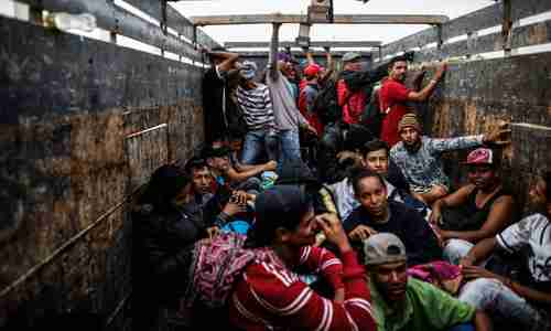 Venezuelan migrants travel aboard a truck in Tumbes, Peru, near the Ecuador border, on 1 November (AFP)