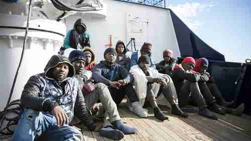 Migrants sit on the deck of the Sea Eye rescue ship in the Mediterranean Sea (AP)